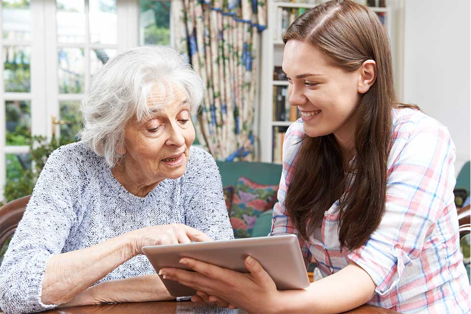 Elderly woman using computer technology to communicate with her loved ones