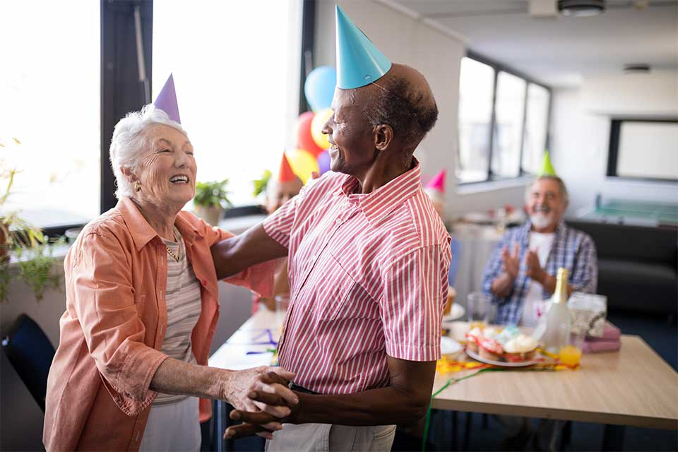 Elderly couple dancing together for a birthday party in a continuing care retirement community.