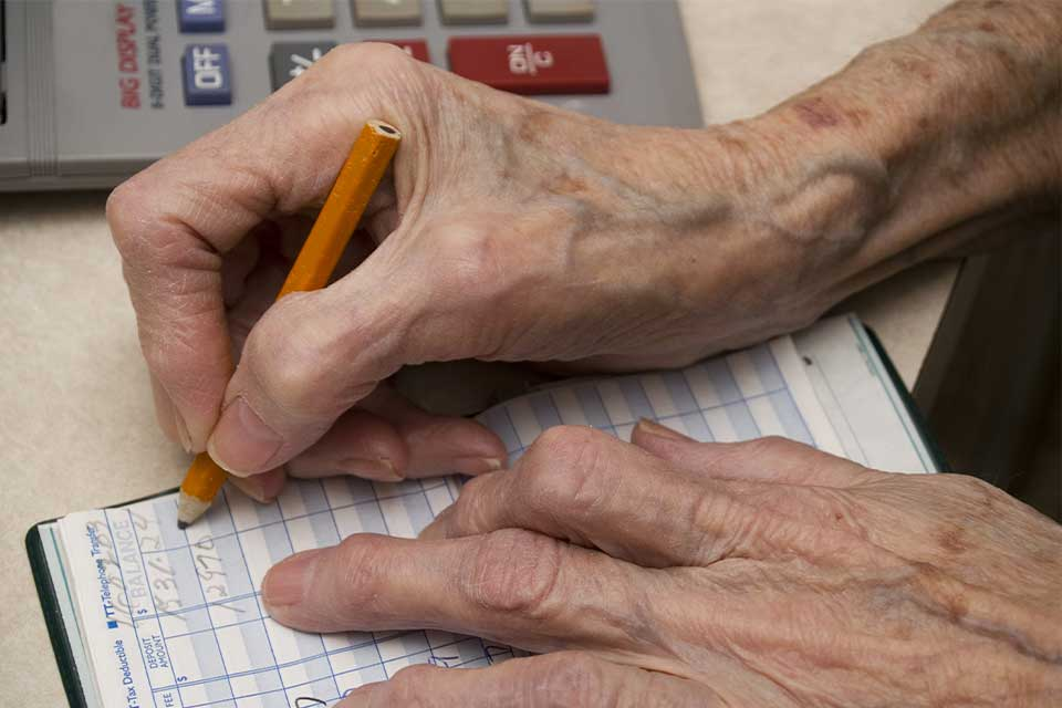 Close-up of senior citizen's hands balancing a checkbook with a calculator and pencil.