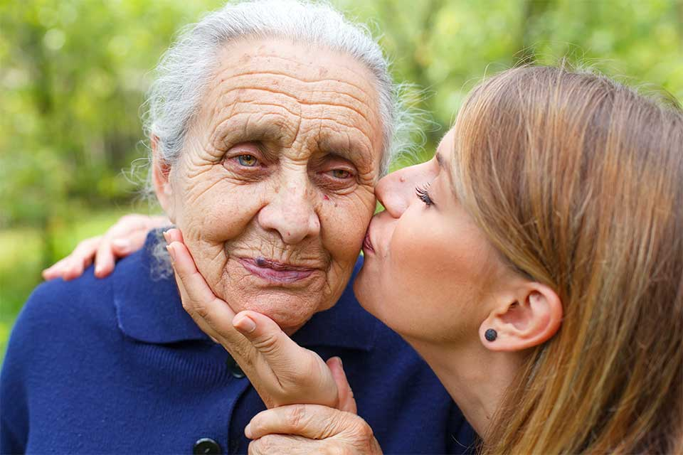 Younger daughter kissing her elderly mother on the cheek