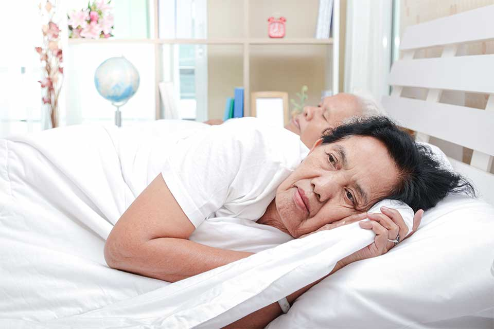 Elderly woman laying next to her husband in bed unable to sleep.