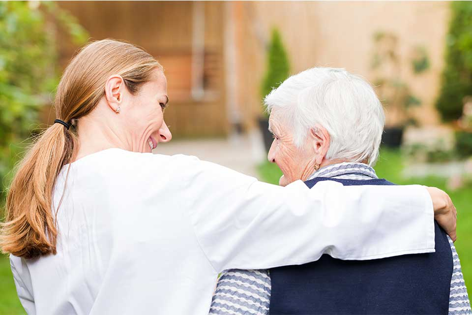 Elderly woman with dementia receiving care from a caregiver.