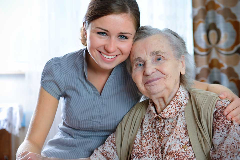 Caregiver and elderly woman with dementia in embrace.