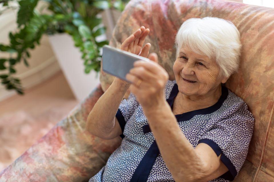Elderly woman talks on the phone.