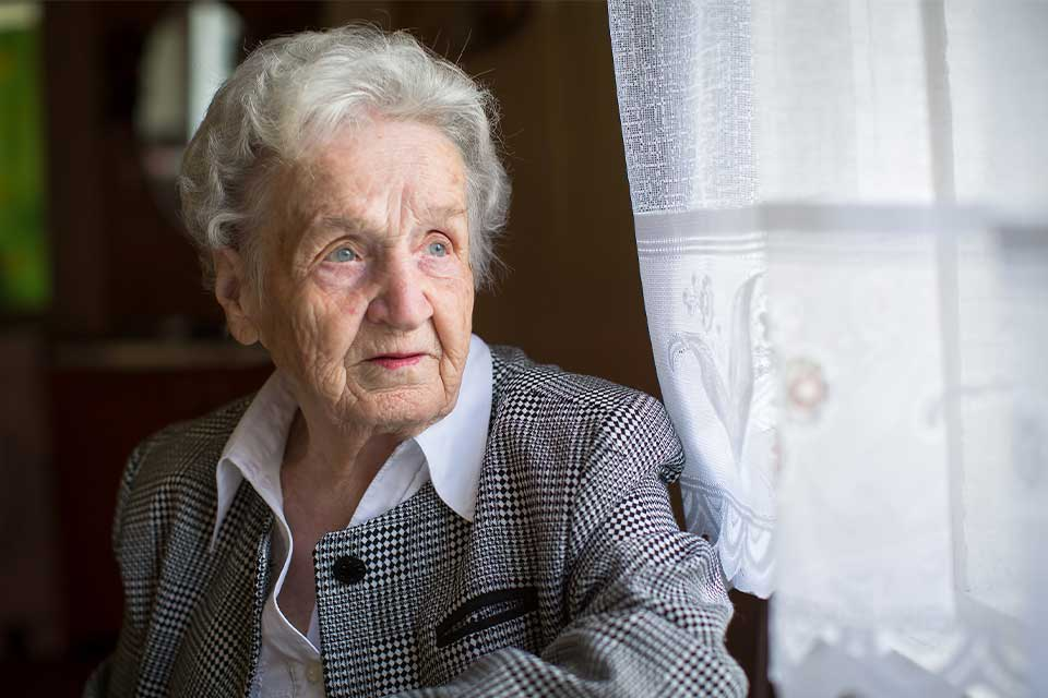 Elderly woman with dementia looking out the window.
