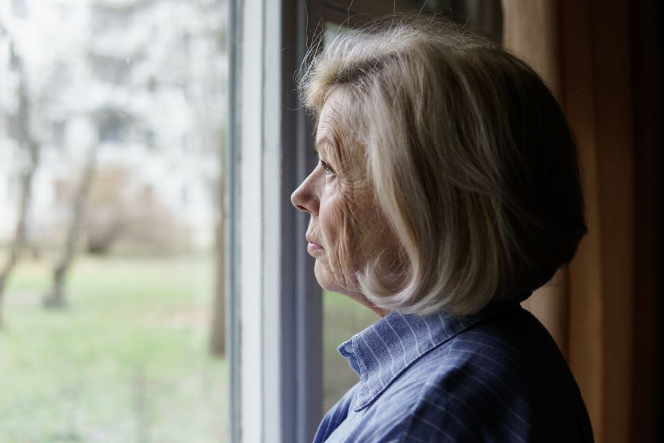Elderly woman with dementia looks out a window.