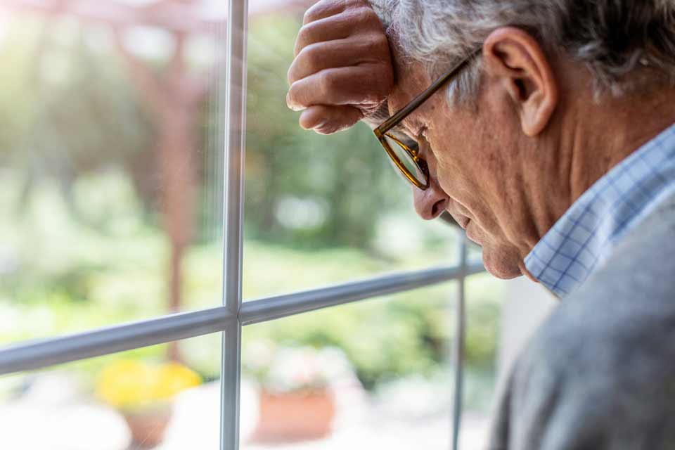 Elderly man leaning against a window in frustration and despair about his dementia symptoms.