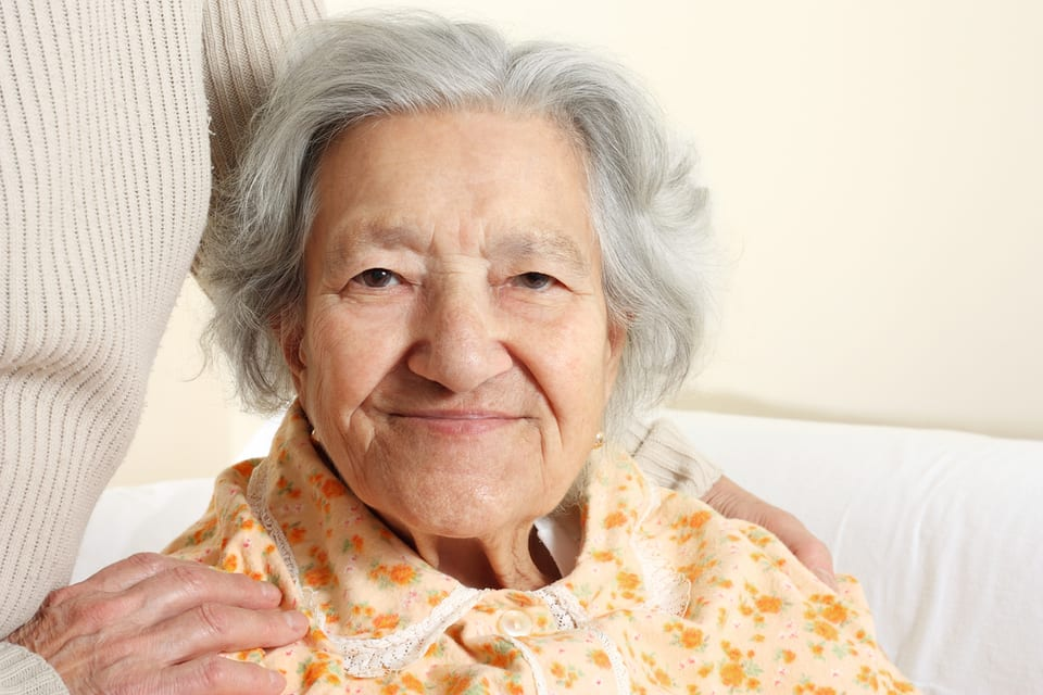 Smiling elderly woman with caregiver