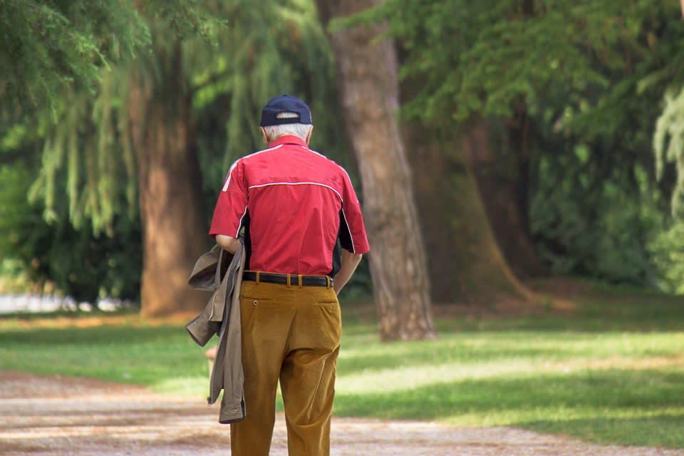 Elderly man with dementia wanders in a park.