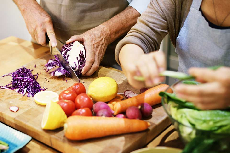 Elderly couple cutting and preparing vegetables.