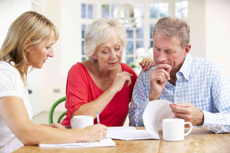 Elderly couple reviewing documents with female advisor