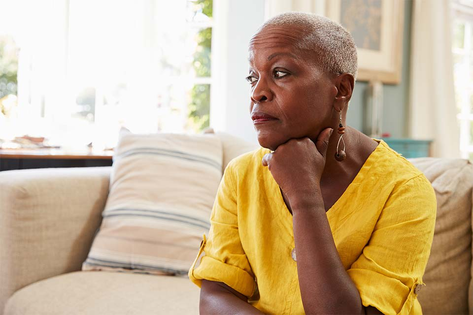 Elderly woman sitting on couch looking off into the distance