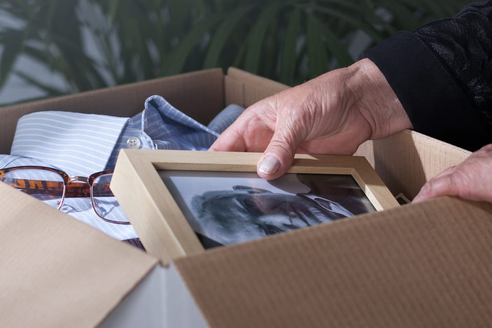 Woman looks at elderly father's picture in moving box.