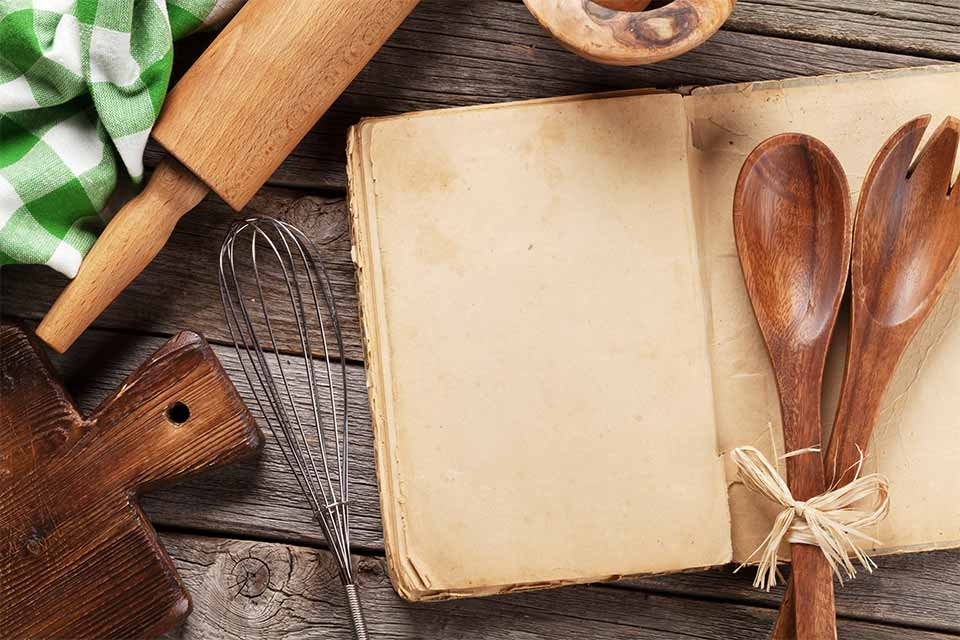 Recipe book surrounded by a rolling pin, cutting board and kitchen towel.