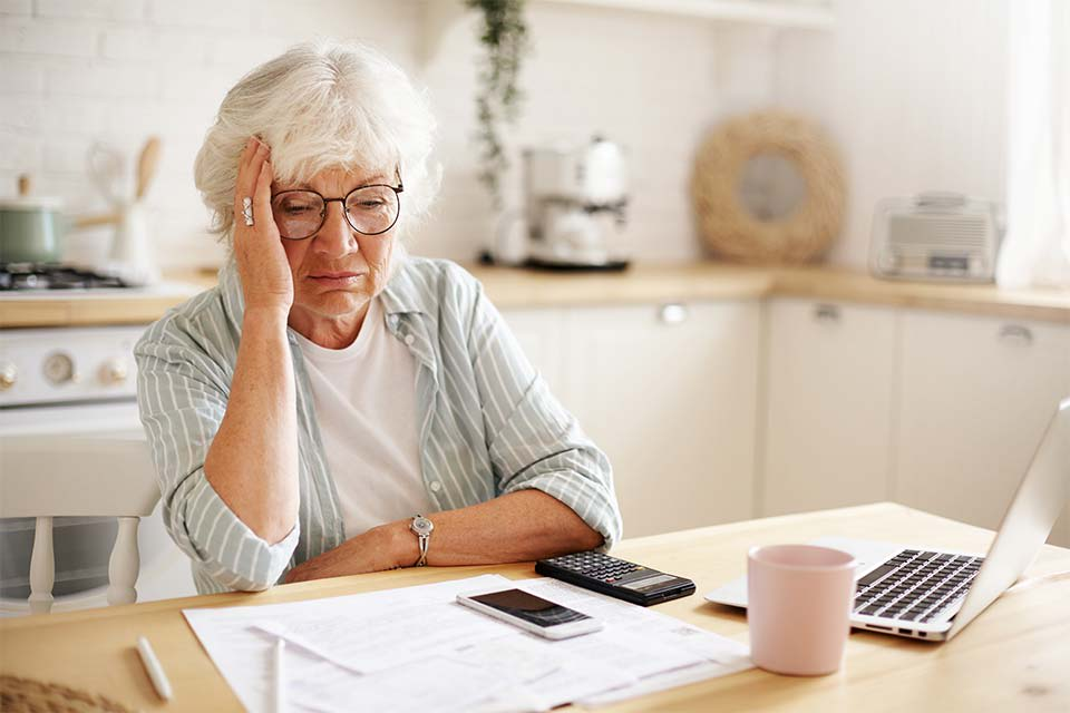 Elderly woman struggling to calculate her potential elder care costs