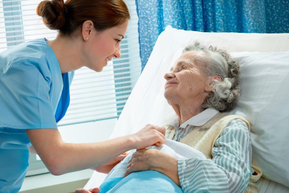 Nurse helping elderly woman in bed
