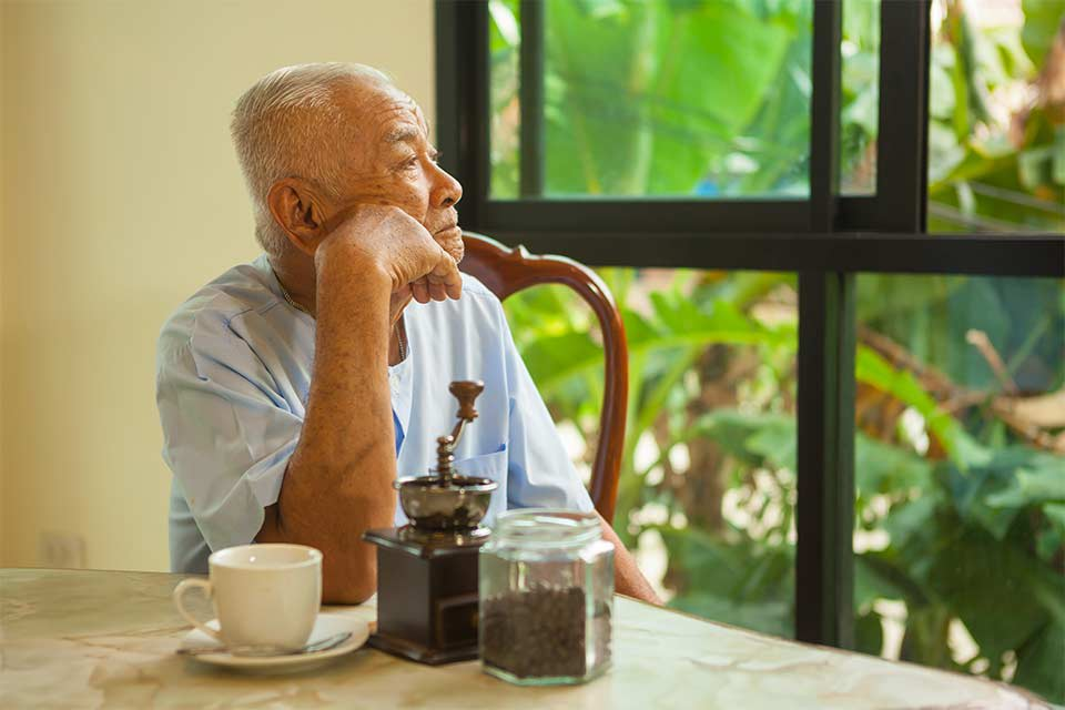 Elderly man with depression looking forlorn, staring out window.