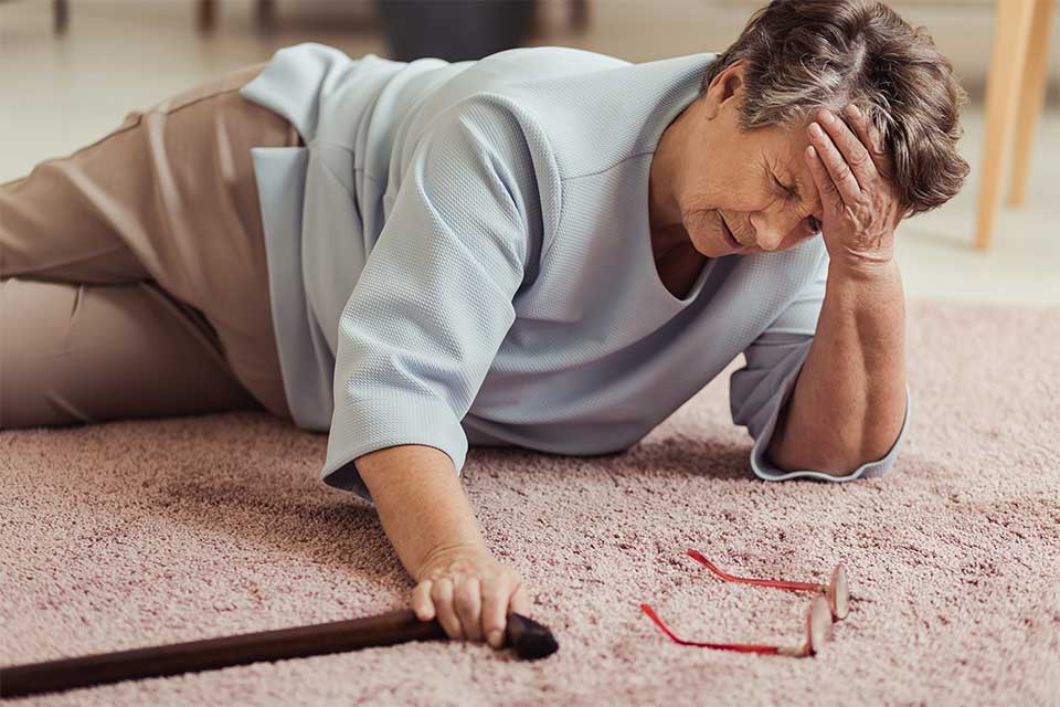 Elderly woman with fractured hip laying on carpet in pain