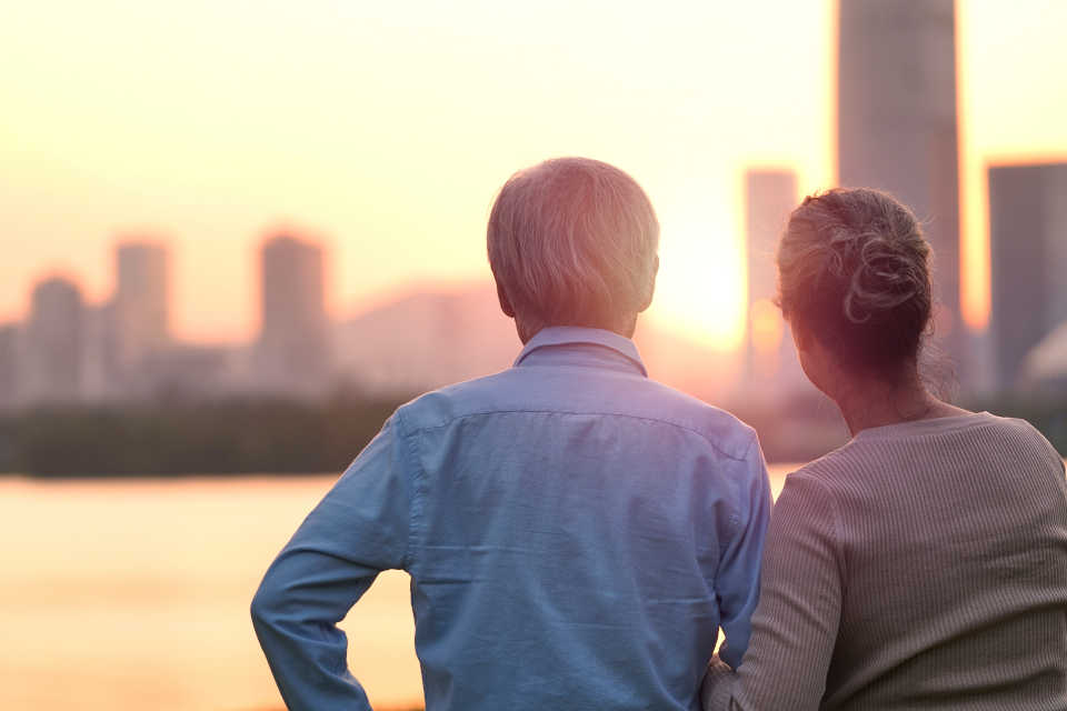 Elderly man with sundown syndrome looking at skyline with his daughter