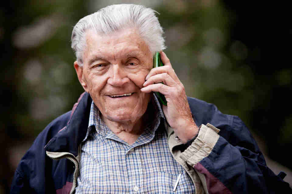 Elderly man in navy blue jacket talking on cell phone.