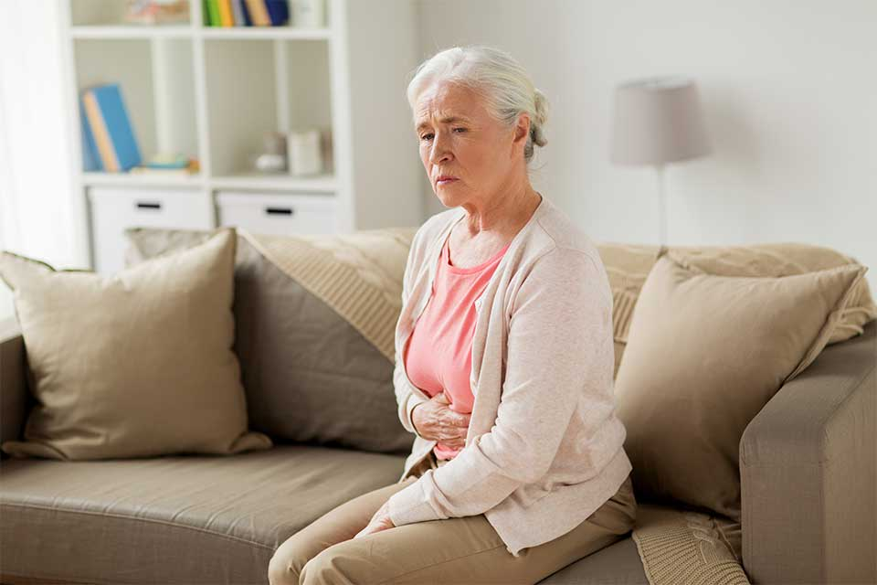 Elderly woman sitting on couch struggling with fecal incontinence.