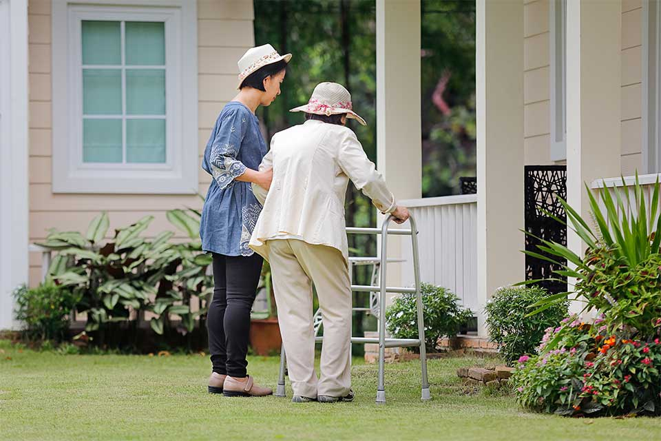 Caregiver helping elderly woman with a walker get to the front door of her house