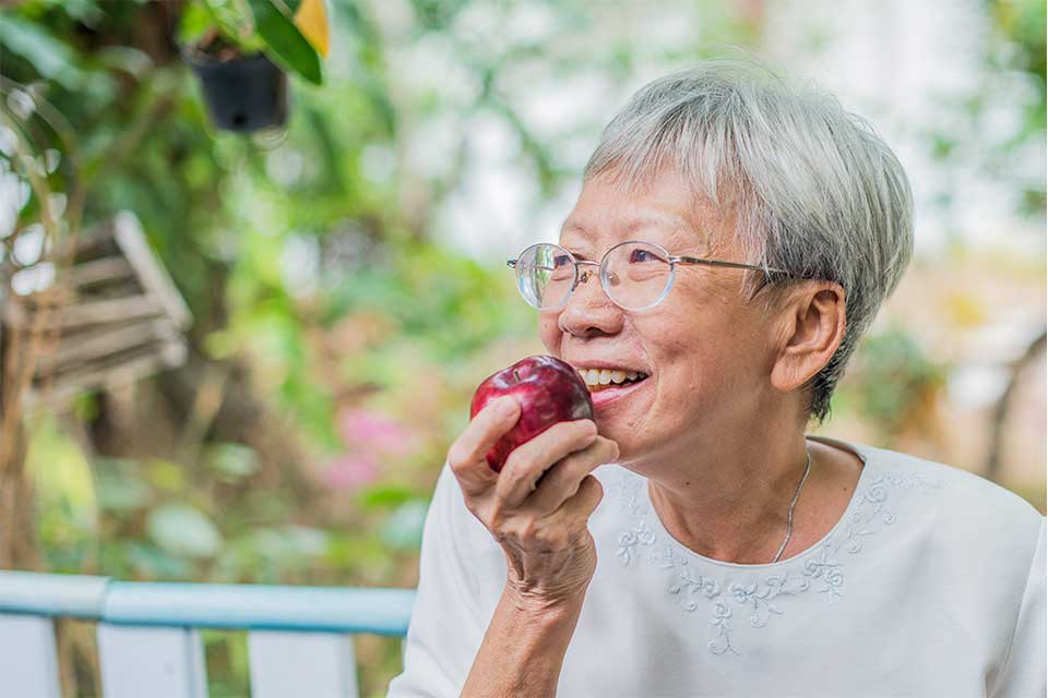 Elderly woman getting ready to take a bit of a red apple.