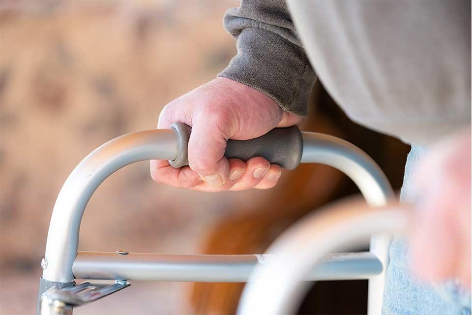 Elderly man using a walker after undergoing a hip replacement.