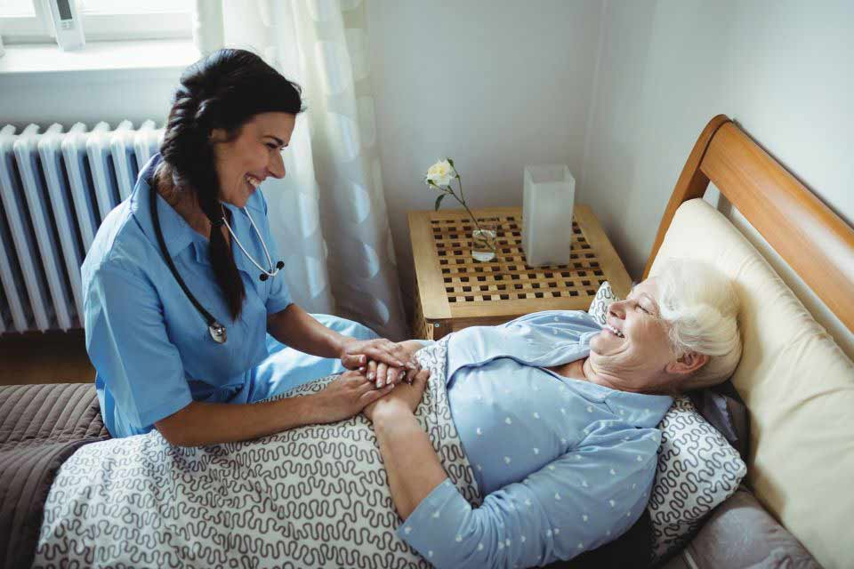 Home care provider taking care of elderly woman in bed.