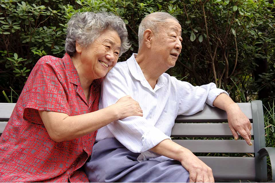 Elderly couple sitting on a park bench near their senior living community.