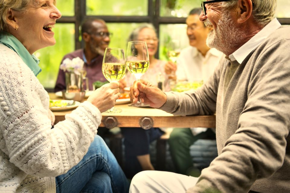 Independent living seniors toast and enjoy the company of friends.
