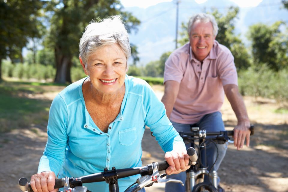 Elderly couple ride bikes together