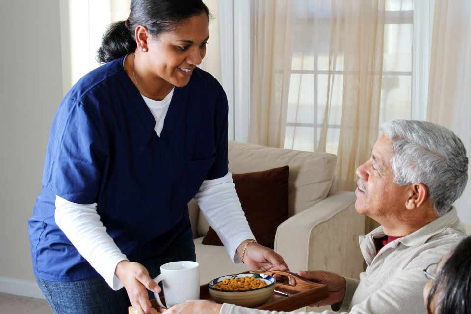 Home care nurse serving a bowl of cereal and coffee to an elderly man.