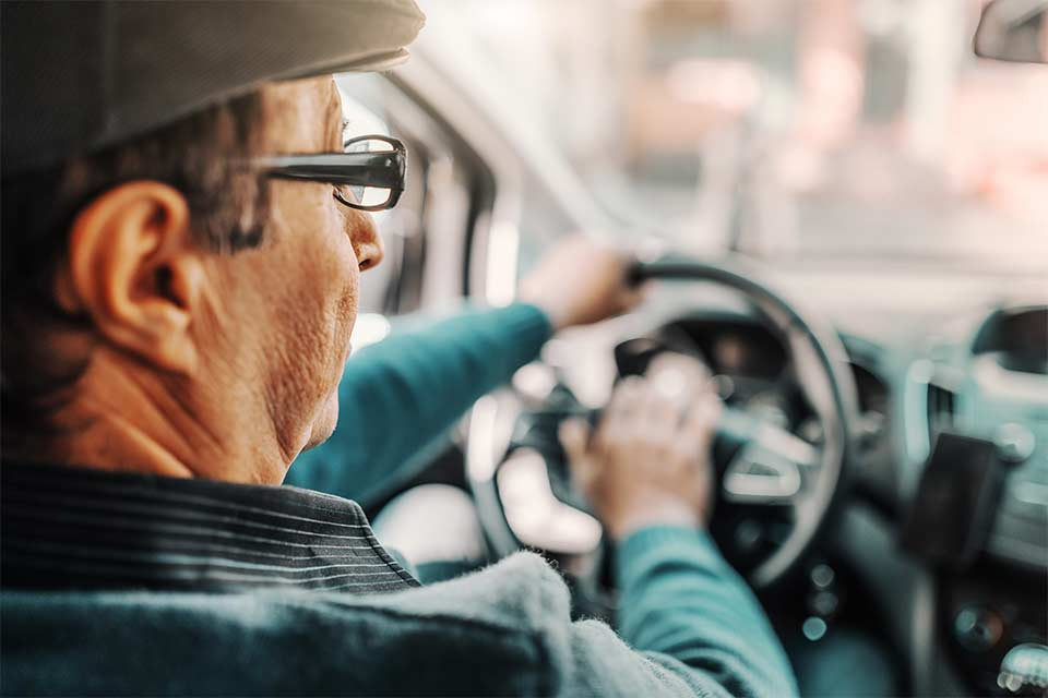 Elderly man driving his car and honking his horn in an attempt to stay safe.n