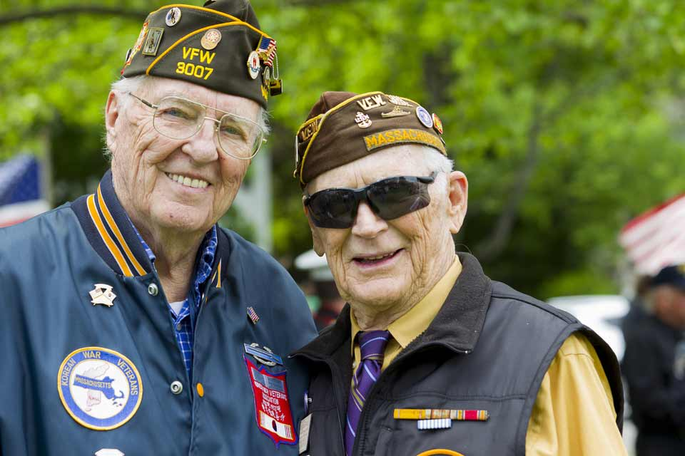 Two military veterans wearing their uniforms and smiling for a picture.