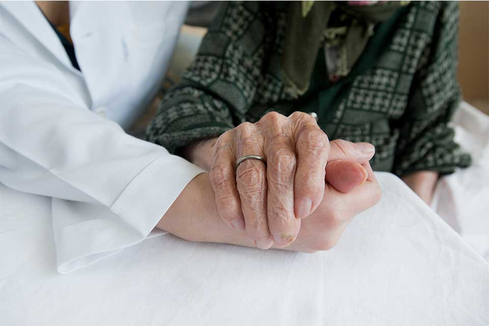 Elderly woman holding a doctor's hand while she learns whether medicare or medicaid will cover her assisted living costs.