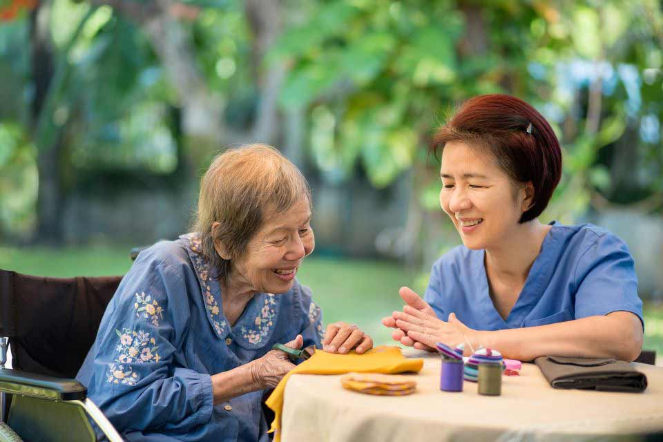 Elderly woman and her caregiver participating in tactile therapy at an outdoor table.