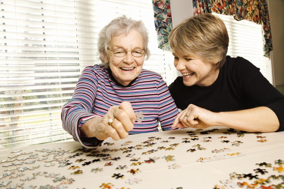 Elderly woman and daughter do a puzzle together at a memory care facility.