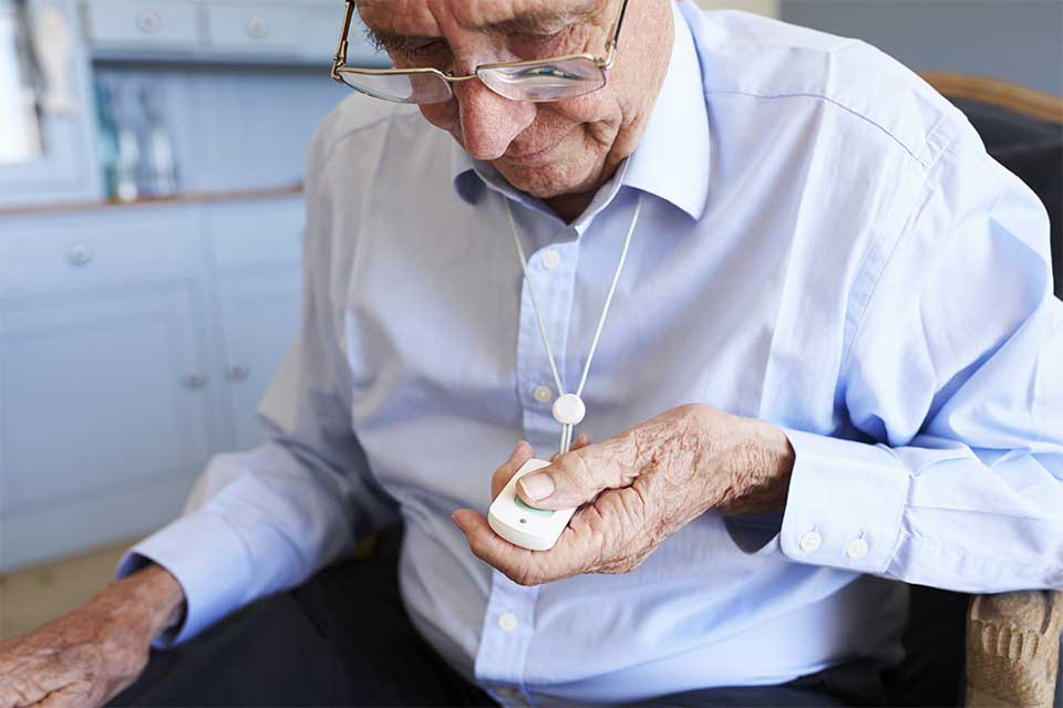 Elderly man pushing his panic button necklace to summon a memory care nurse.