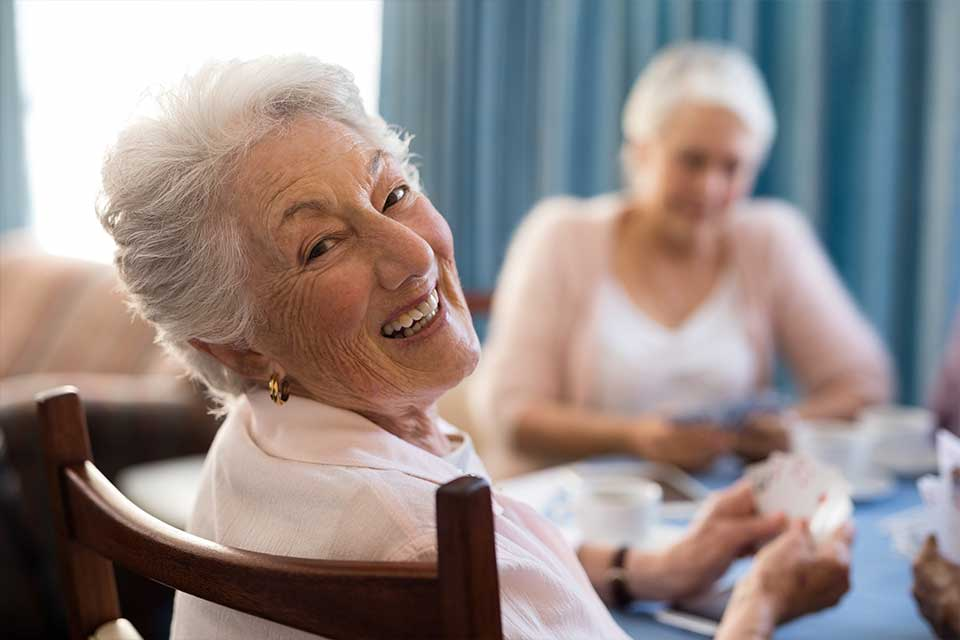 Elderly women playing cards in a senior living facility.