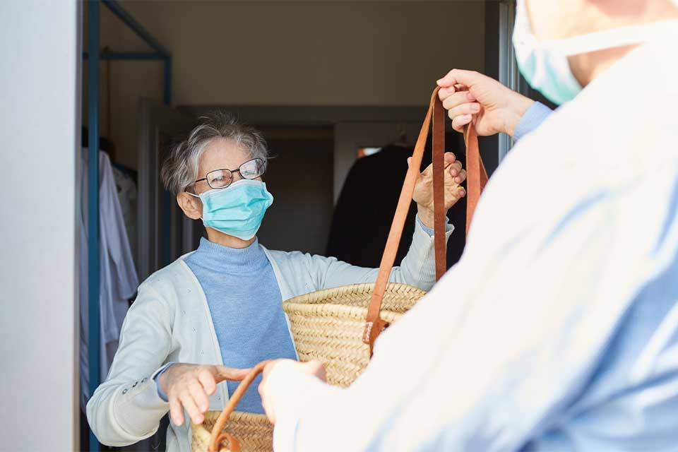 Elderly woman in mask exchanging bags with masked senior living employee.