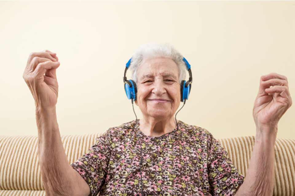 Elderly woman wearing headphones, listening to music and moving her arms to its rhythm.