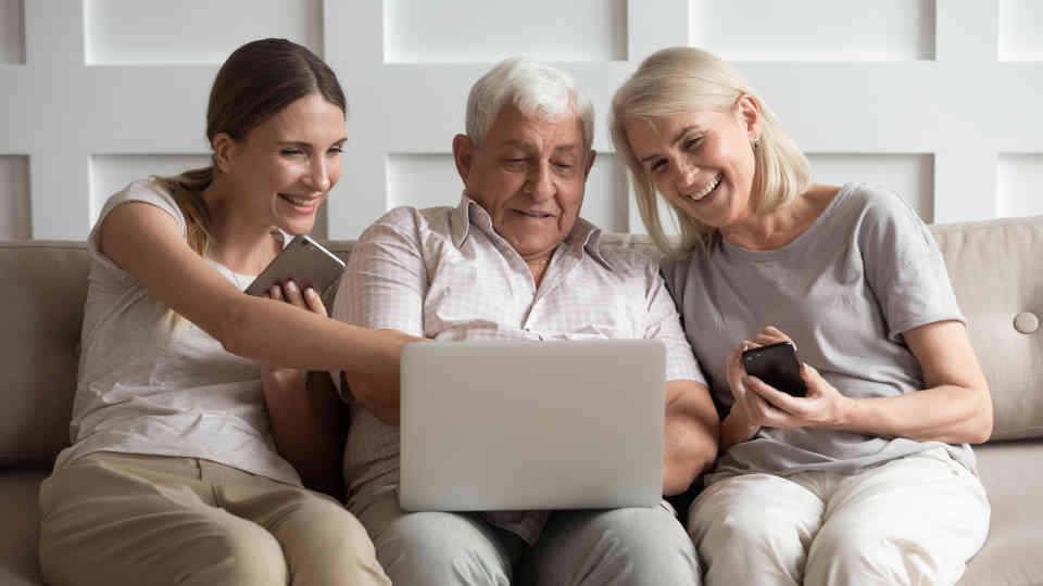 Daughter helping parents look at assisted living facilities on a laptop