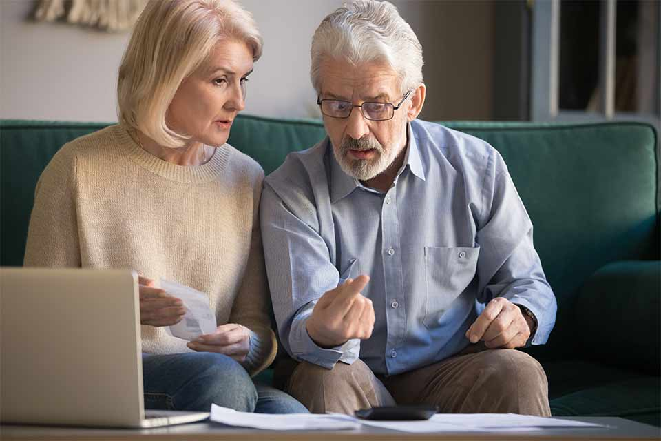 Elderly couple using a calculator and laptop to figure out how to pay for home care services.