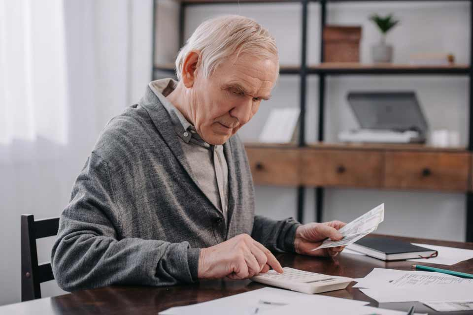 Elderly man at his desk doing calculations by hand and paying medical bills.