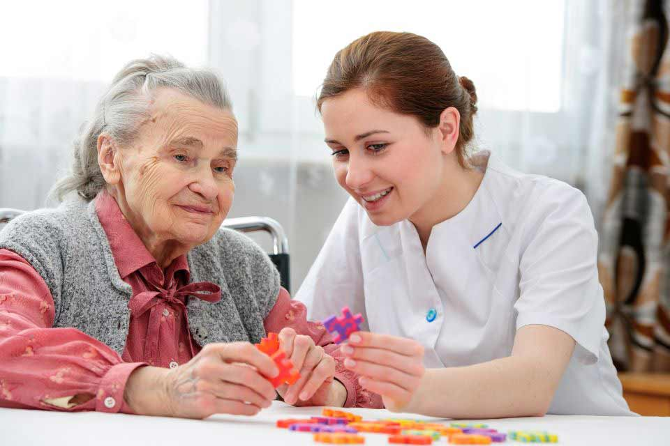 Elderly woman getting help from a caregiver to put together a puzzle.
