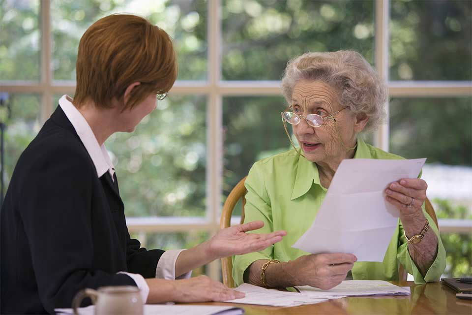 Elderly woman visiting with her attorney about power of attorney matters.