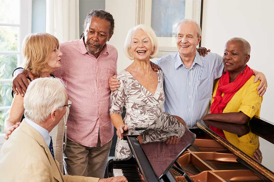 Group of elderly adults standing around a piano singing songs
