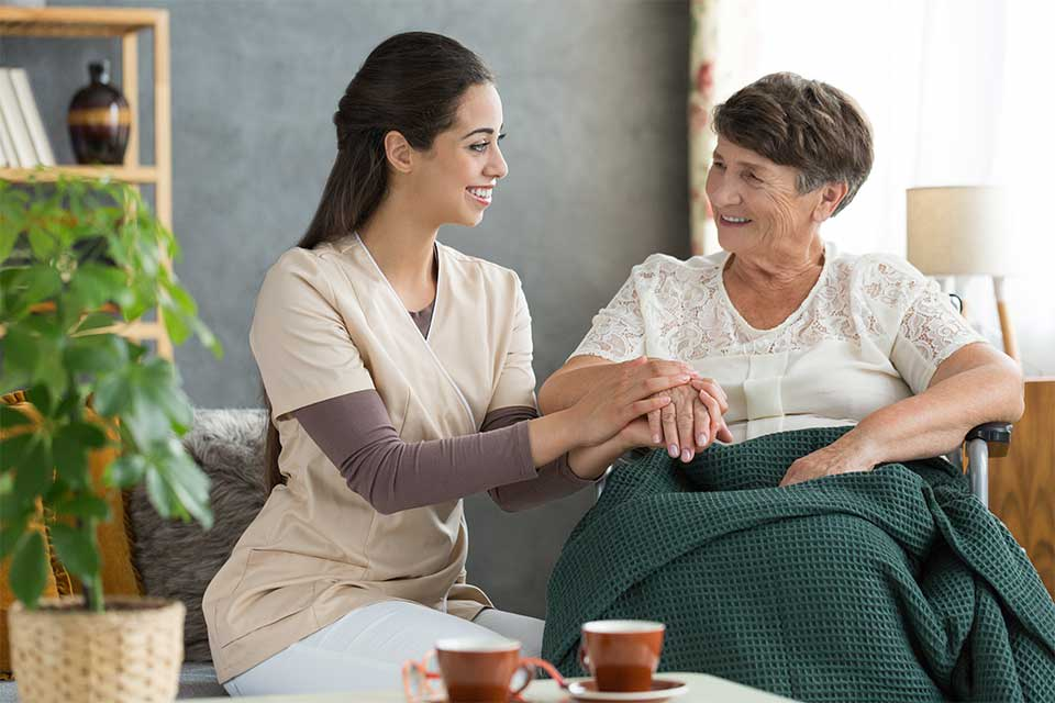 Caregiver taking care of elderly female patient in respite care