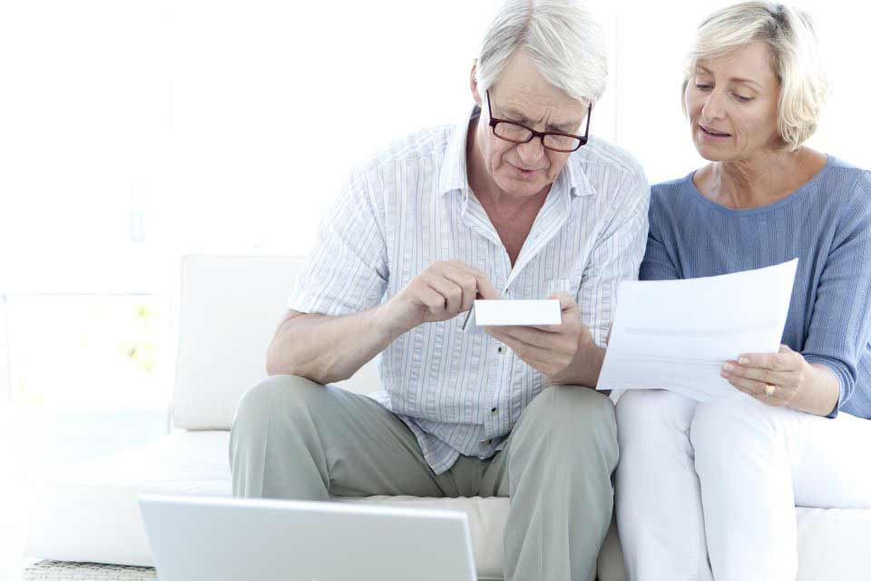 Elderly couple sitting on a couch calculating costs of moving to a retirement community.